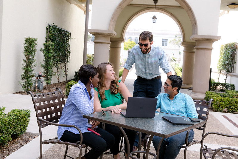 Four graduate students gather around a laptop at a table outside at the University of San Diego