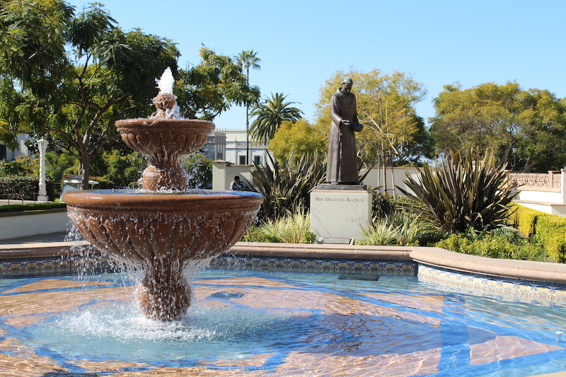 Water emerges from fountain on University of San Diego campus with a statue of a priest in the background