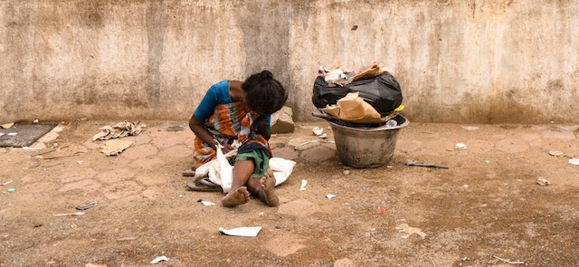 woman sitting on ground with no shoes near trash