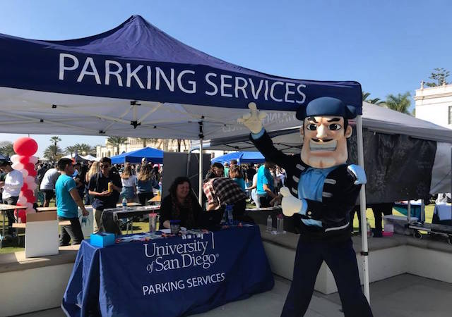 Diego Torero pointing to USD Parking Services sign-up tent